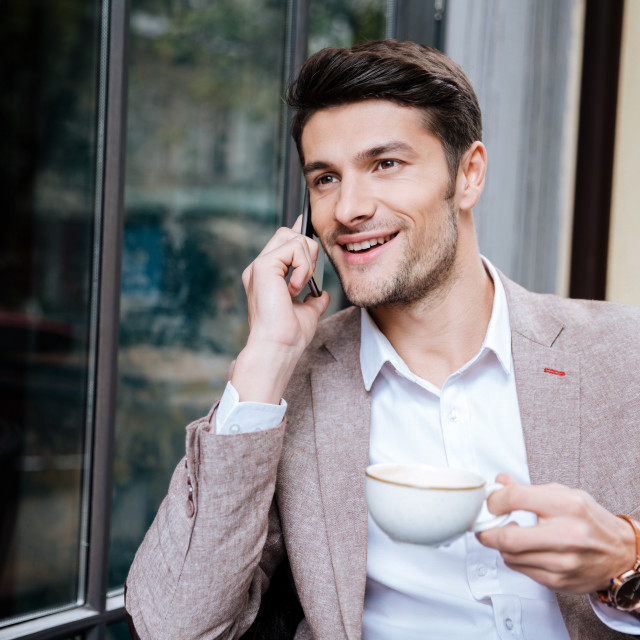 """Smiling young businessman talking on mobile phone in outdoor cafe"" stock image"