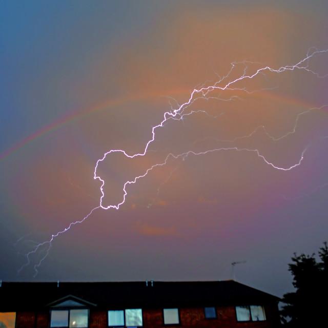 """Lightning strikes through the heart of a rainbow"" stock image"