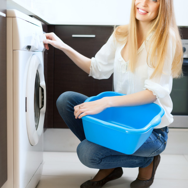 """Long-haired woman using washing machine"" stock image"