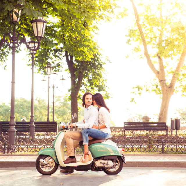 """""""Sideview of a trendy couple riding a scooter in the morning. Sun is shining..."""" stock image"""