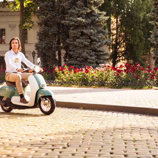 """""""Confident young man riding a scooter through town streets in the morning"""" stock image"""