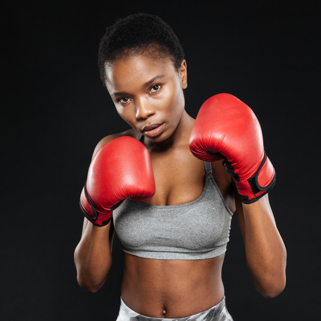 """Fitness girl in boxing gloves fighting on black background"" stock image"