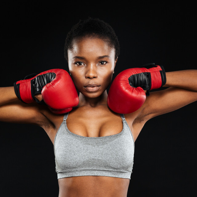 """Portrait of a beautiful fitness woman standing in boxing gloves"" stock image"