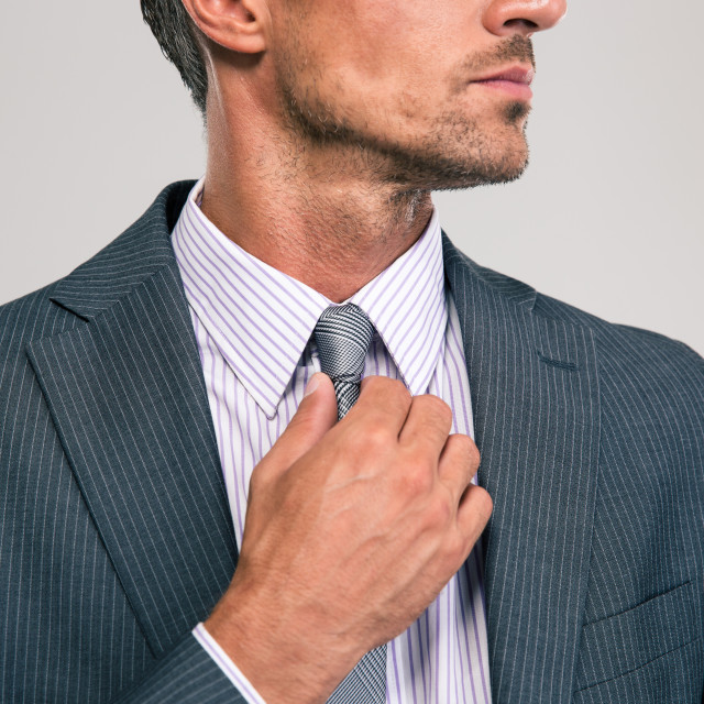"""Businessman straightening his tie"" stock image"