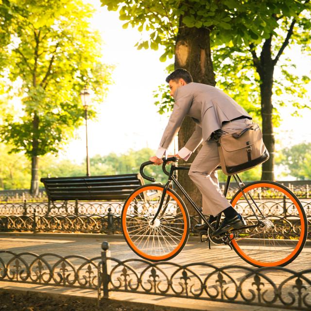 """Businessman riding bicycle"" stock image"