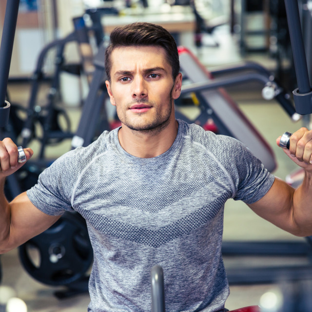 """""""Bodybuilder workout on fitness machine at gym"""" stock image"""
