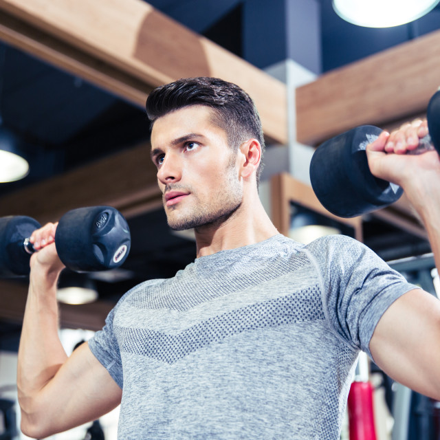 """""""Man doing exercises with dumbbells at gym"""" stock image"""