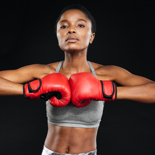 """Fitness woman posing with boxing gloves on black background"" stock image"