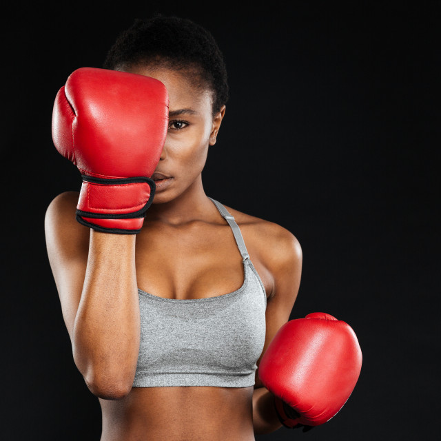 """Strong young fitness woman covered her face with boxing gloves"" stock image"