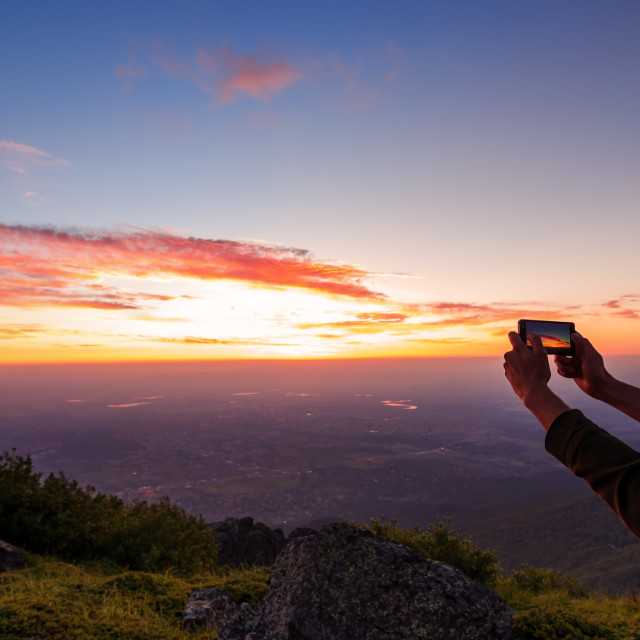 """hand shooting the sunrise over the city in Bulgaria"" stock image"