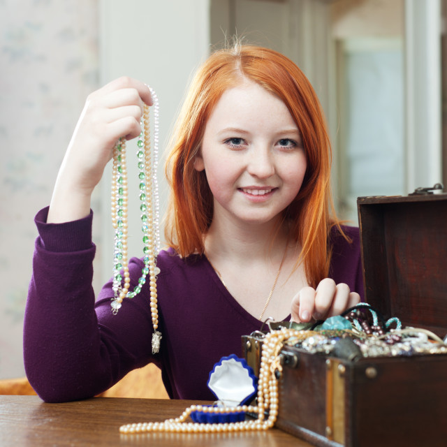 """girl chooses necklace in treasure chest"" stock image"