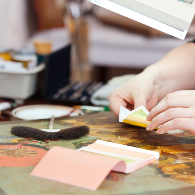 """""""Art restorer gilding on the ancient icon"""" stock image"""