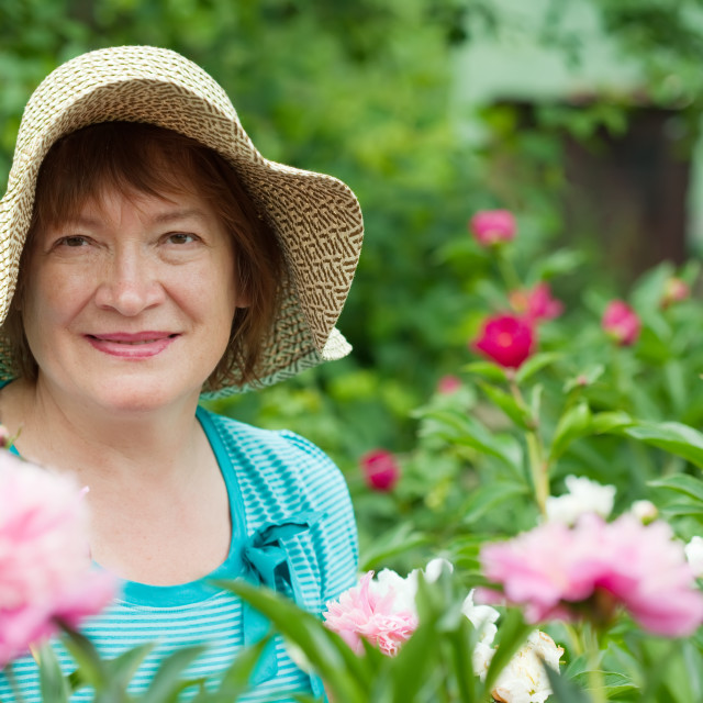 """""""Happy mature woman with peony plant"""" stock image"""