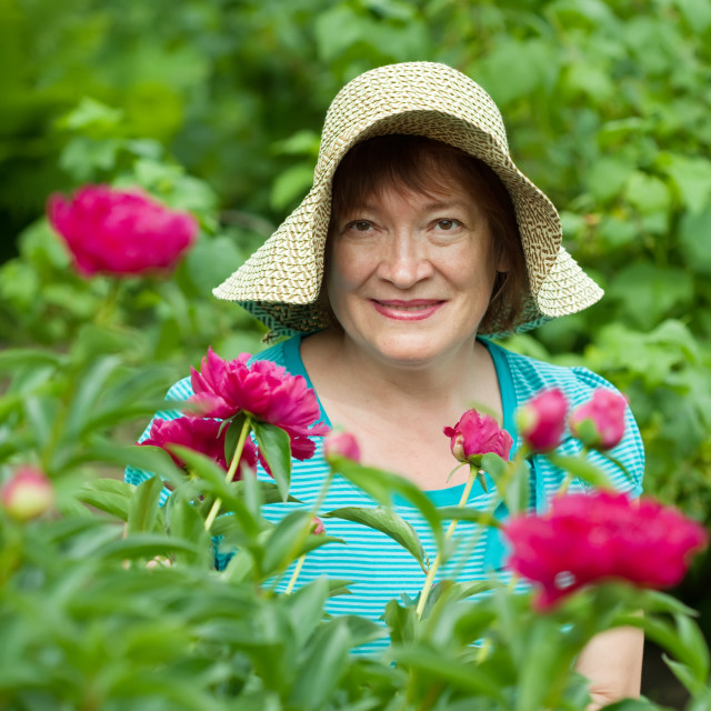 """""""Happy mature woman in paeony plant"""" stock image"""