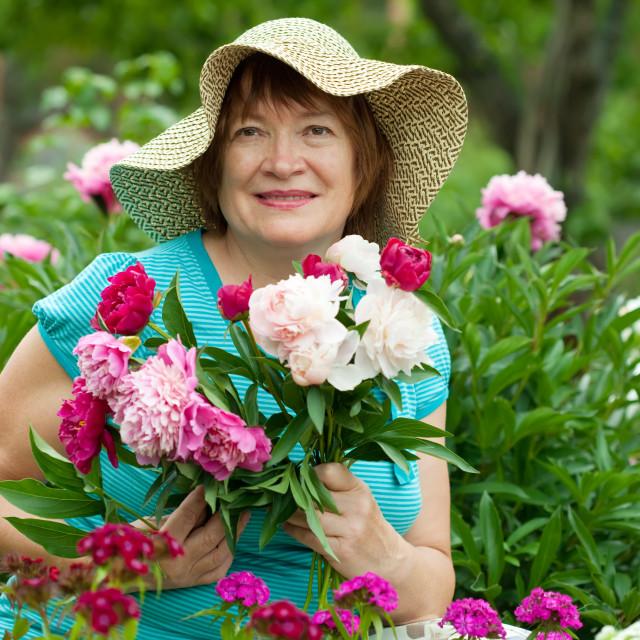 """Happy mature woman in garden"" stock image"