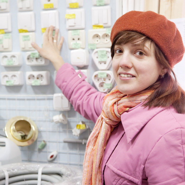 """""""woman chooses switch in electrical store"""" stock image"""