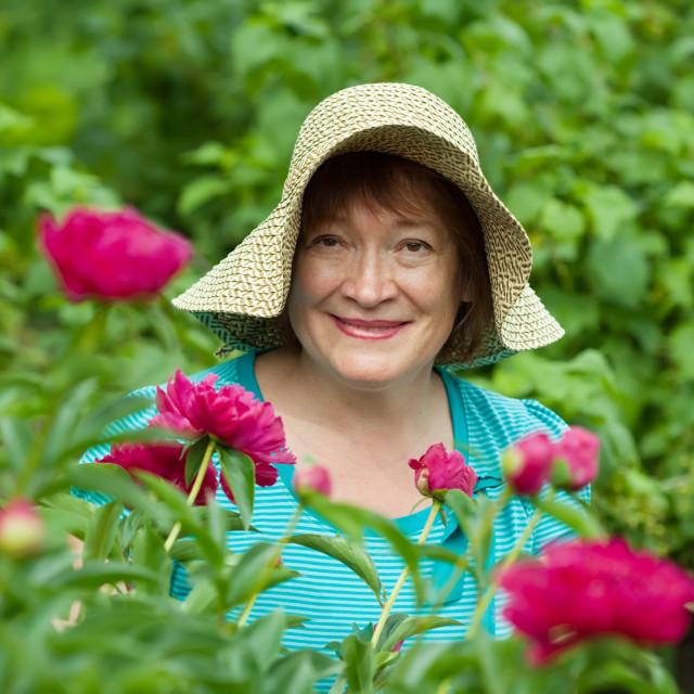 """Happy female gardener in flowers"" stock image"