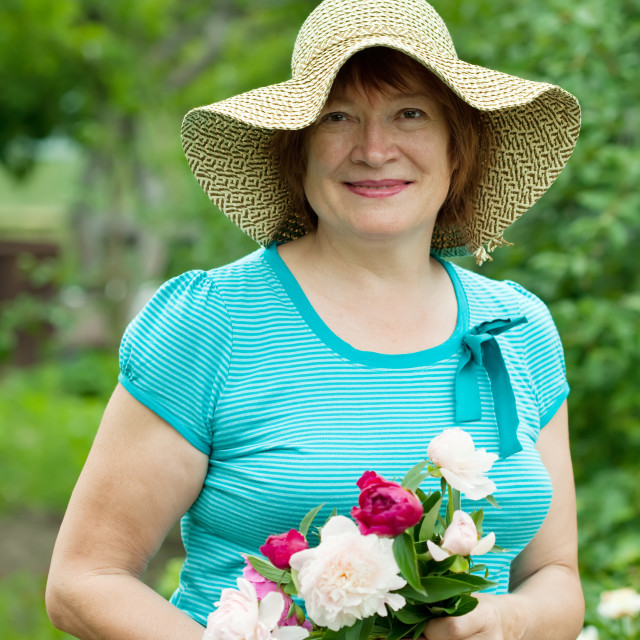 """""""Happy mature woman with peony"""" stock image"""