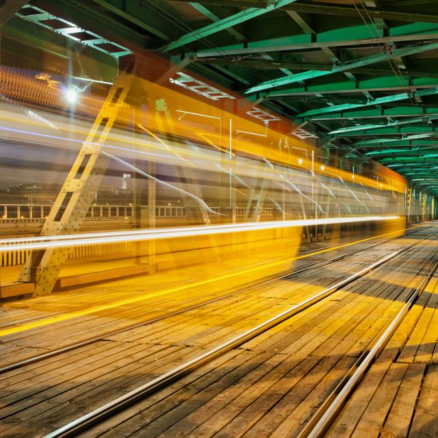 """Steel Truss Bridge with Tram Light Trail"" stock image"