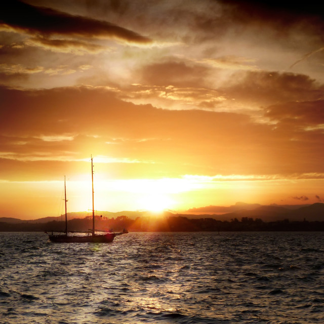 """Sailboat sailing by sunset"" stock image"