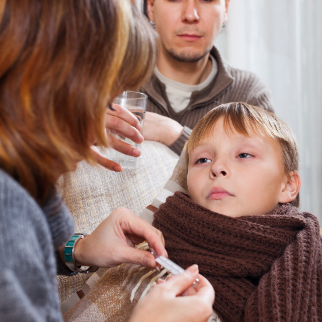 """Parents measuring the temperature of unwell son"" stock image"