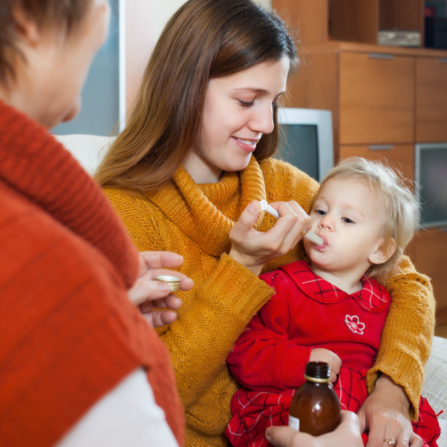 """Two women caring for unwell toddler"" stock image"