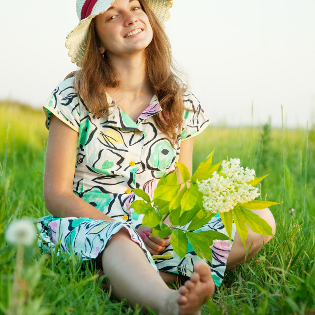 """girl in hat is sitting on meadow"" stock image"