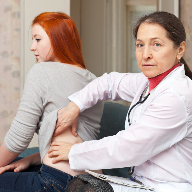 """Mature physician touching behind of patient"" stock image"