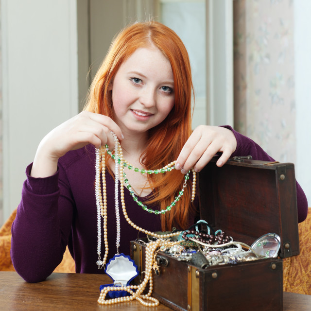 """teen girl looks jewelry in treasure chest"" stock image"