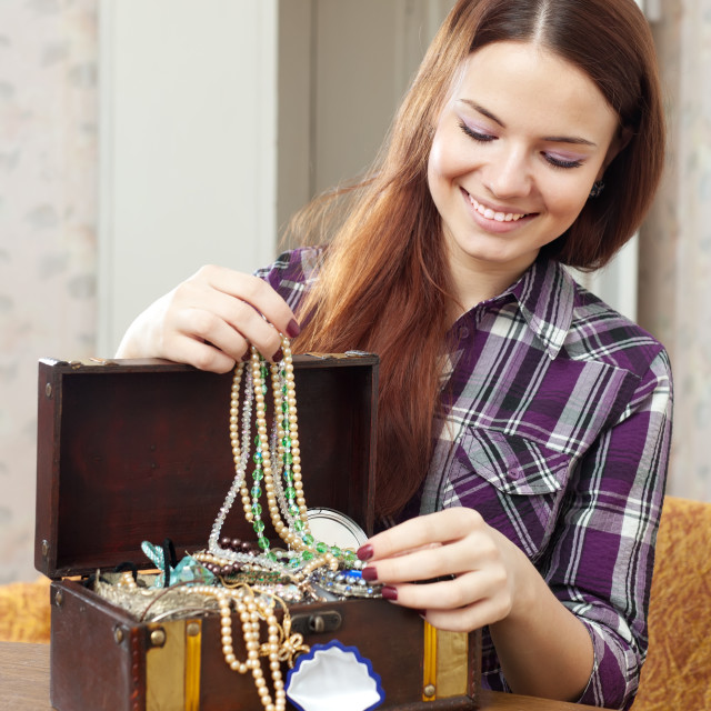 """happy girl chooses jewelry in treasure chest"" stock image"