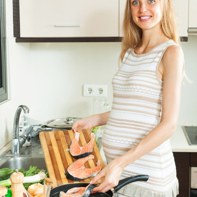 """""""Happy pregnant woman cooking salmon"""" stock image"""