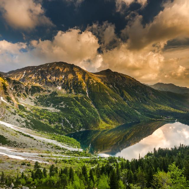 """dramatic sky at sunrise over alpine lake in Tatra"" stock image"
