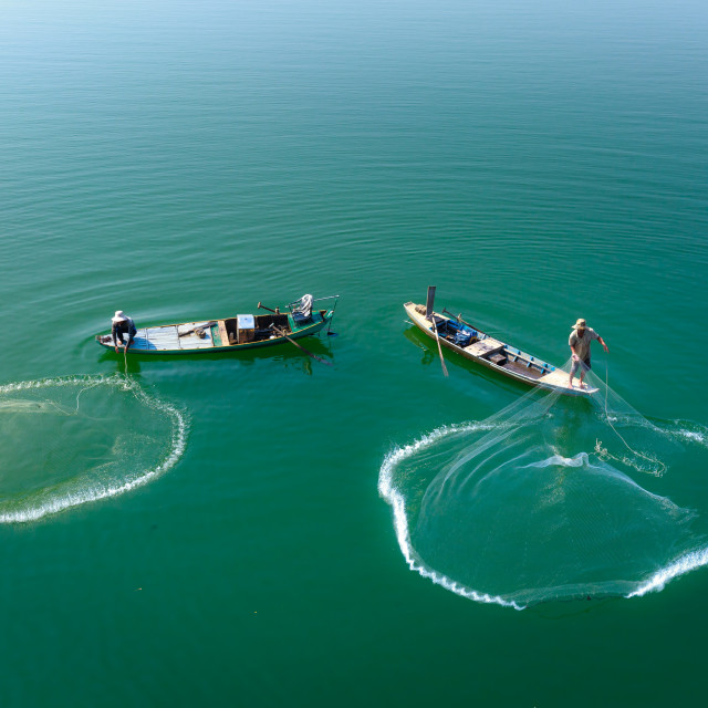 """casting a net to catch fish on Tri An Lake"" stock image"
