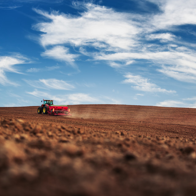 """Farmer with tractor seeding crops at field"" stock image"