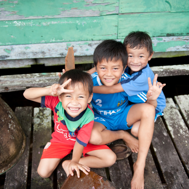 """Smiling children outside their longhouse, Sibu, Sarawak, Borneo"" stock image"