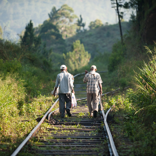 """Two workmen walking down a train track, Sri Lanka"" stock image"