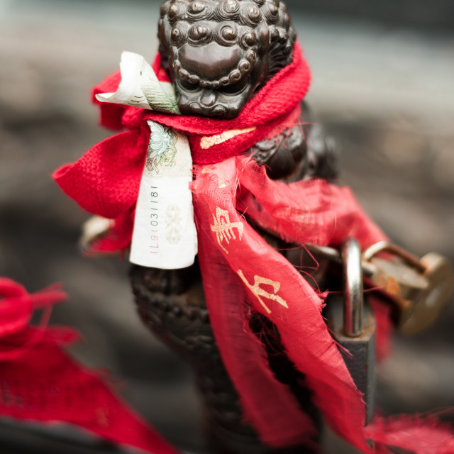"""Red ribbons and money tied around a Chinese dragon sculpture"" stock image"