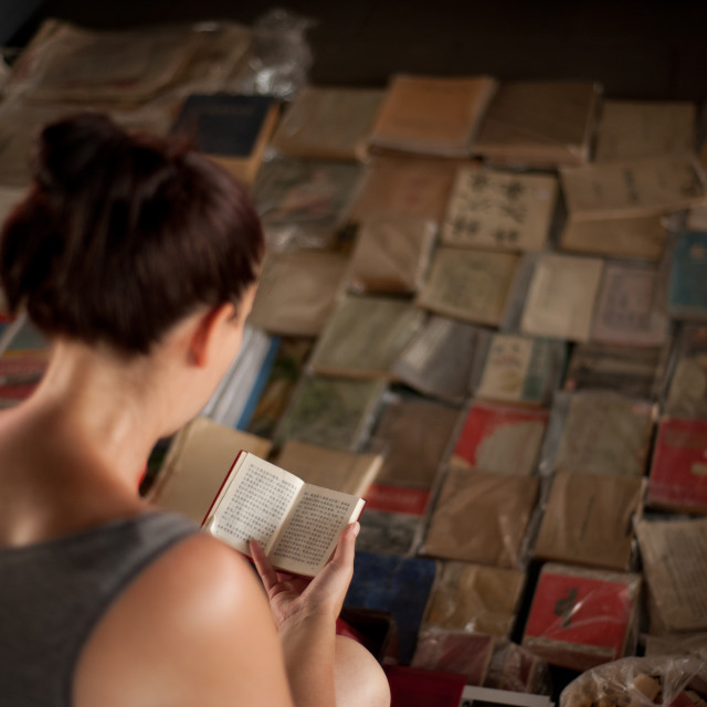 """""""A female tourist looks at 'Chairman Mao's little red book', Beijing, China"""" stock image"""