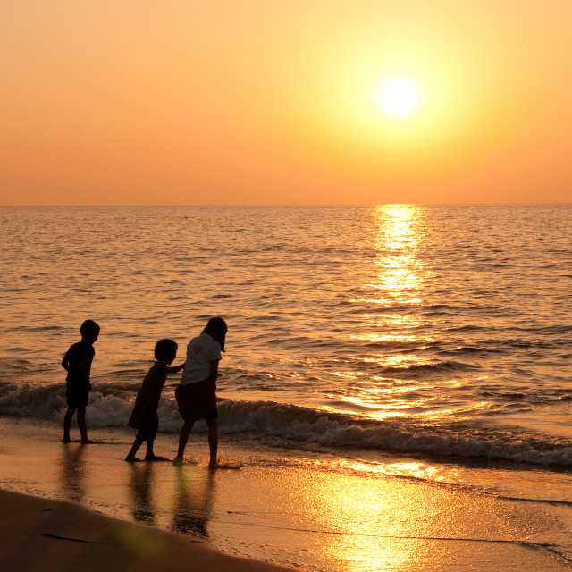 """Playing on the beach as the sun sets, Cochin, India"" stock image"