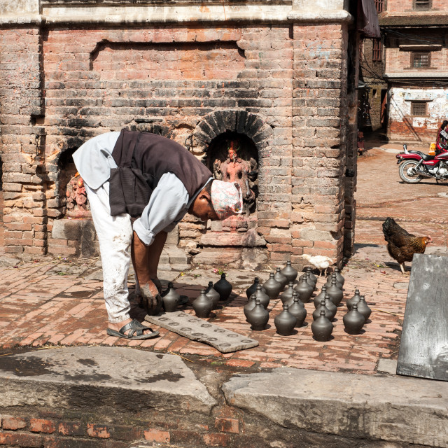 """Man inspecting his pots, Kathmandu, Nepal"" stock image"