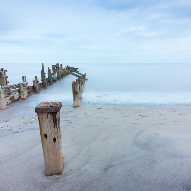"""Weathered groynes in the sand"" stock image"