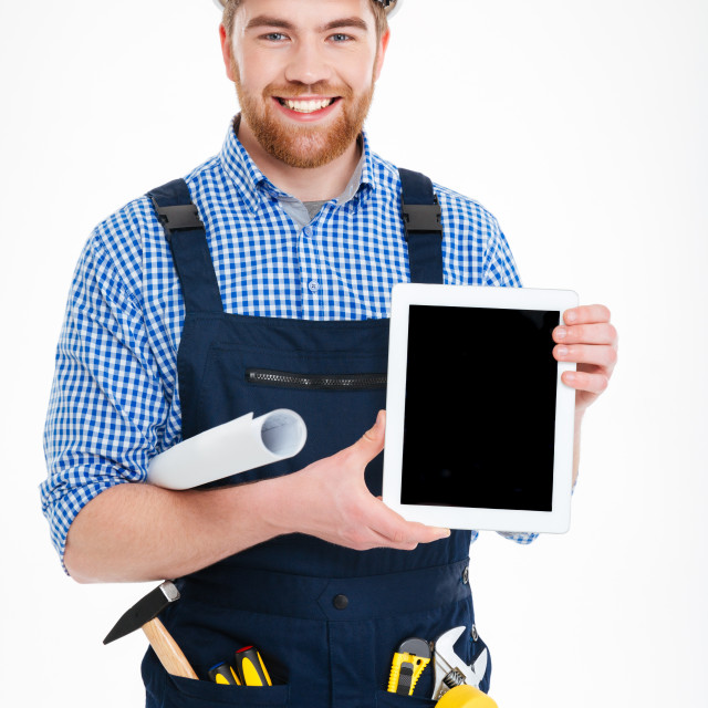 """""""Smiling handsome young builder holding blank screen tablet"""" stock image"""