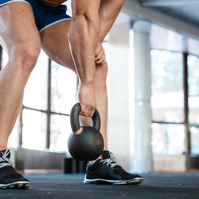 """Sporty man hands and legs lifting kettle ball"" stock image"