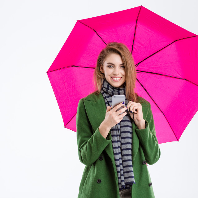 """Woman holding smartphone under umbrella"" stock image"