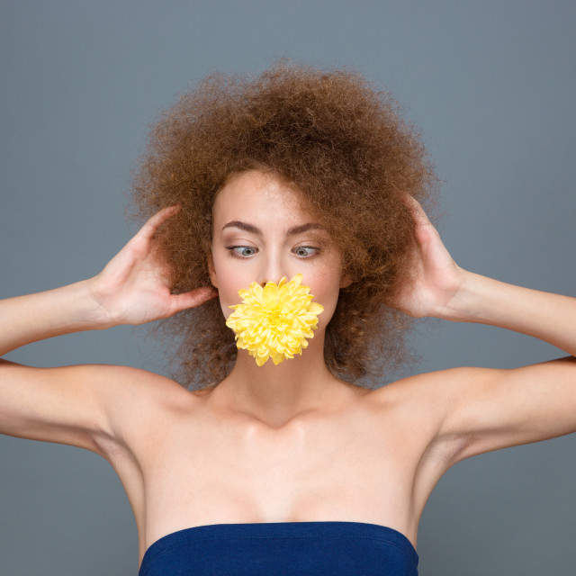 """Amusing curly girl with flower in mouth kidding and squinting"" stock image"