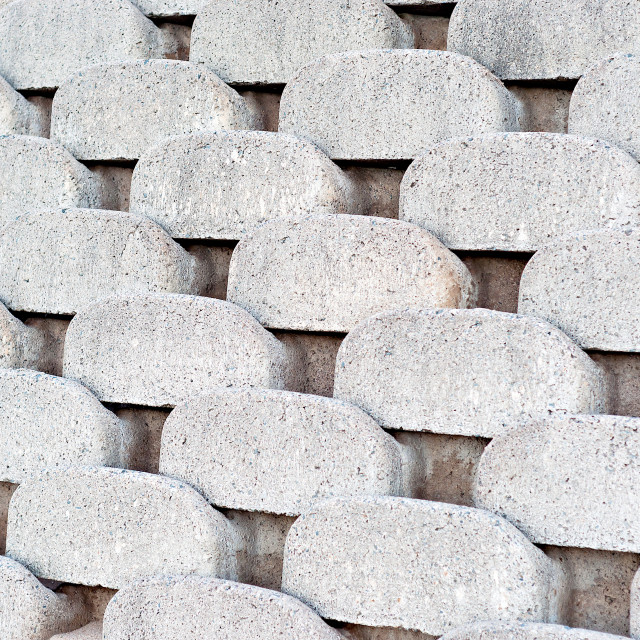 """Close up patterns and textures of curved interlocking concrete retaining wall bricks"" stock image"