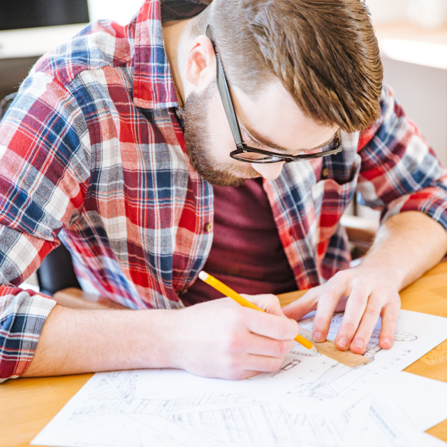"""""""Serious hardworking student sitting at the desk and drawing blueprint"""" stock image"""