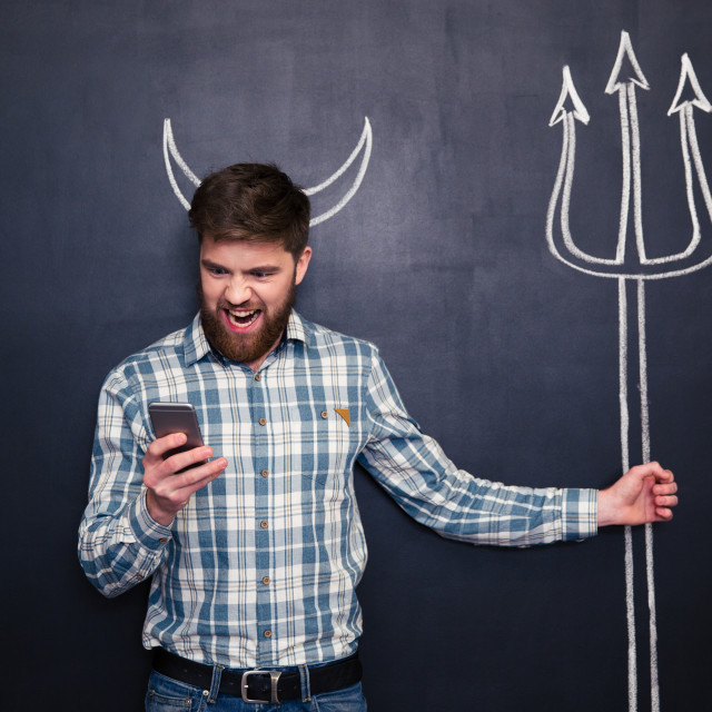 """""""Handsome man playing role of devil standing over blackboard background"""" stock image"""