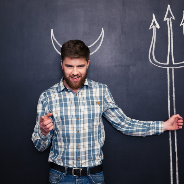"""""""Man holding trident and pointing on you over blackboard background"""" stock image"""