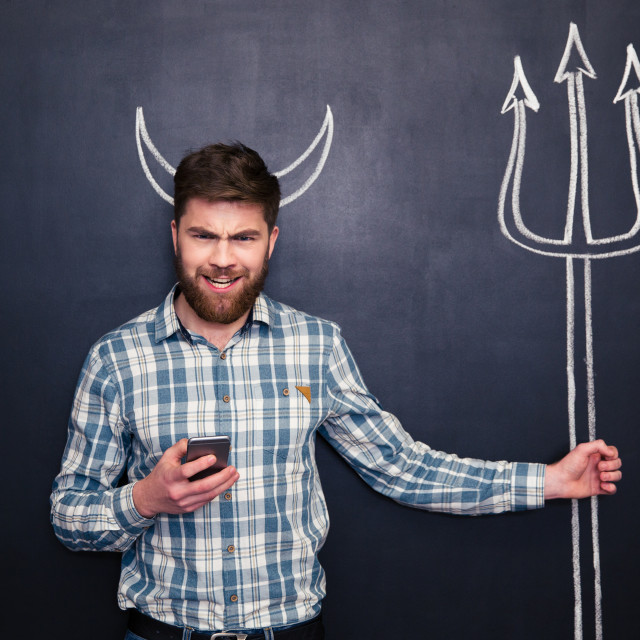 """Bearded man using smartphone standing over blackboard background"" stock image"